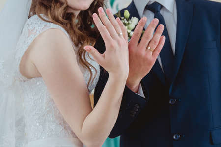 Bride and groom show their hands with wedding rings. Shallow depth of field. Stock Photo