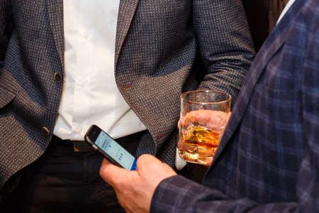 Cropped image of man holding whisky and smartphone while resting in restaurant. Shallow depth of field.