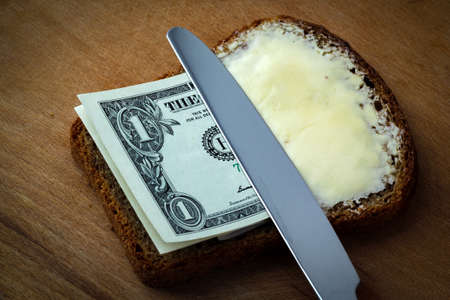 Butter and money on a slice of bread and knife Archivio Fotografico