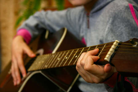 Close up of a teen musician playing acoustic guitar. Shallow depth of field