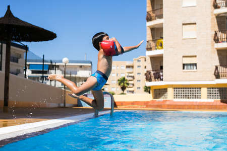 Cute young boy jumping into a swimming pool while on a fun vacation