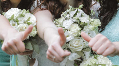 Caucasian bride and two bridesmaids showing thumb up on open air. Shallow depth of field.  Foto de archivo