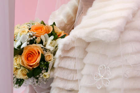 Close up of bride in a fur coat with a bouquet and a veil