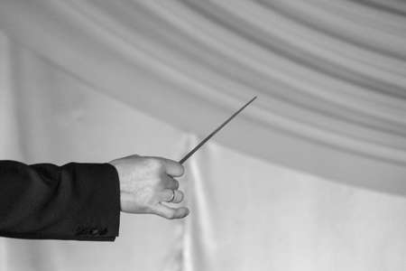 Hand of Orchestra conductor with baton on light background