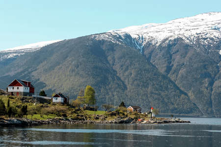 Houses by the lake surrounded with mountains in Norway 写真素材