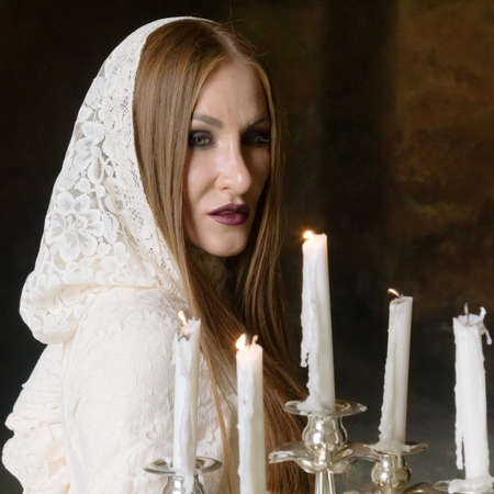 Mysterious woman in dress with candles