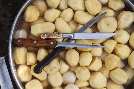 Kitchen knives lay on a raw peeled potatoes in big pot. Top view. Stock Photo