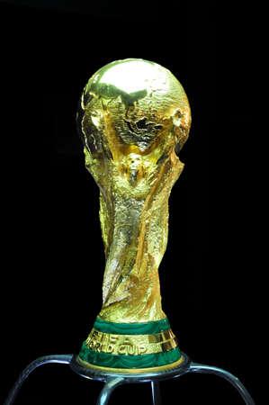 SARAJEVO, BOSNIA AND HERZEGOVINA - MARCH 2014: World Cup Trophy on a black Background, World Cup Trophy, was introduced in 1974. Made of 18 carat gold with a malachite base. Banco de Imagens - 136695530