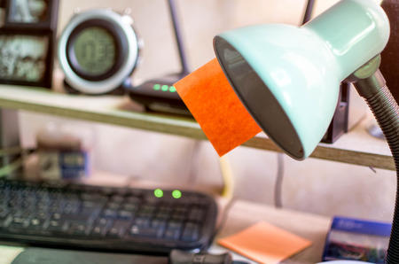 Simple workplace with office lamp showing on it an orange sticky note paper and a black keyboard and a router switched on all on desk table
