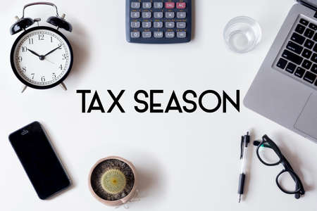 Tax Season words written on white table with clock, smartphone, calculator, pen, cactus, glass and laptop