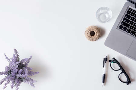 White office desk table with laptop, smartphone, pen, lavender, rope, and glass. Top view with copy space, flat lay.