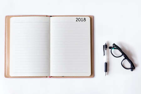 Conceptual,notebook on a white table. open diary and pen with 2018 words Stock Photo