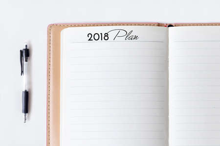 Conceptual,notebook on a white table. open diary and pen with 2018 plan words