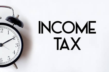 Income tax return word written on white office desk table with alarm clock. Фото со стока