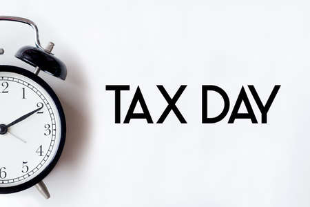 Tax day word written on white office desk table with alarm clock. Stock Photo
