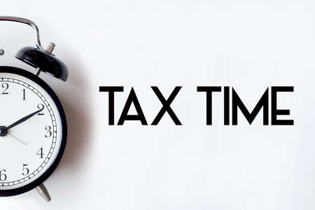Tax time word written on white office desk table with alarm clock.