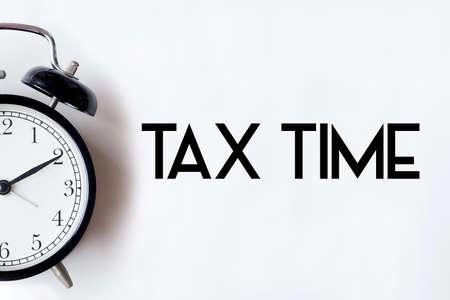 Het woord van de belastingstijd op witte bureaulijst wordt geschreven met wekker die.