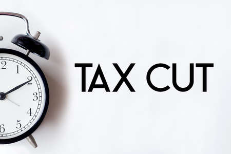 Tax cut word written on white office desk table with alarm clock. Фото со стока