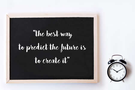 Motivational quote to create future on nature abstract chalkboard and alarm clock. The best way to predict the future is to create it.