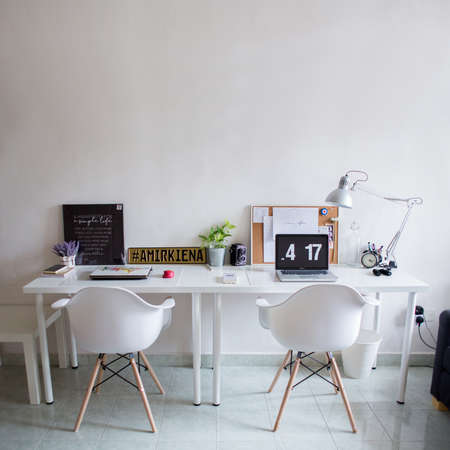 KUALA LUMPUR, MALAYSIA - AUGUST 10, 2017: Macbook and board with magic mouse on white desk. Workspace white white.