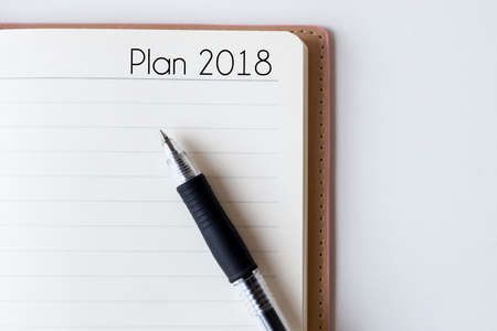 Conceptual,notebook on a white table. open diary and pen with plan 2018 words