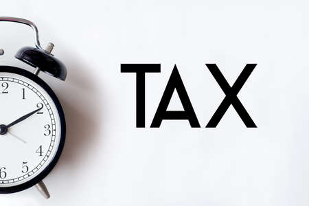 Tax word written on white office desk table with alarm clock.