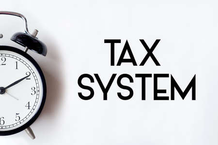 Tax System word written on white office desk table with alarm clock. Фото со стока