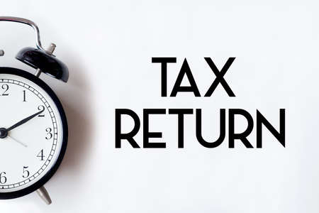 Tax return word written on white office desk table with alarm clock.