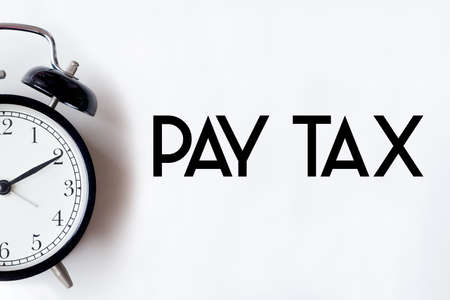 Pay tax return word written on white office desk table with alarm clock.