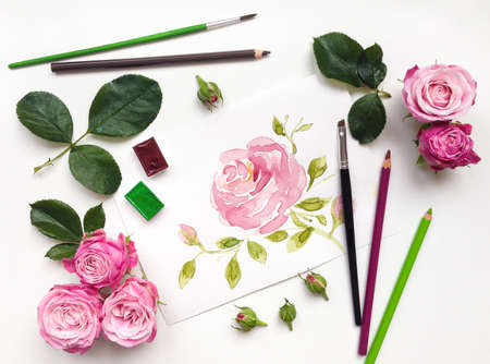 flower leaf: Colorful composition with roses and painting accessories. Flat lay on white table, top view Stock Photo