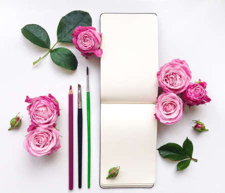 Colorful composition with sketchbook, roses and pencils. Flat lay on white table, top view Stock Photo