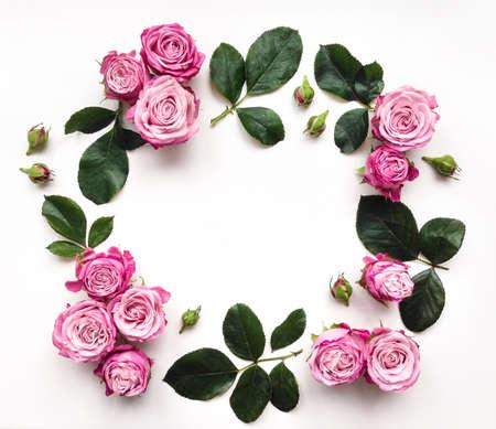 明るいピンクのバラと白い背景の上の葉の装飾的なフレーム。フラットを置く 写真素材