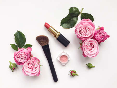 flat brush: Decorative flat lay composition with cosmetics and flowers. Flat lay, top view on white background