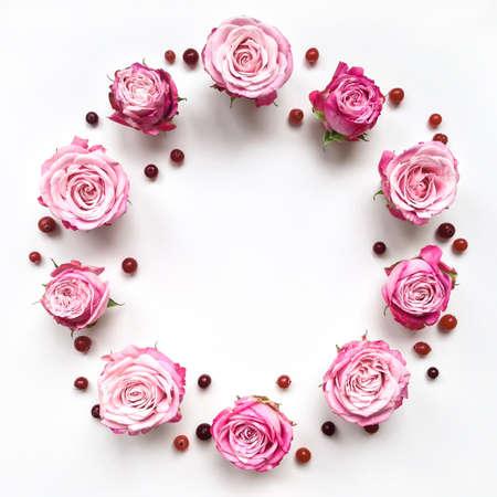 明るいピンクのバラと白い背景の漿果を持つ装飾的なフレーム。フラット レイアウト構成