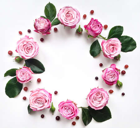 Decorative frame with pink bright roses and berries on white background. Flat lay