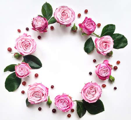 rosas blancas: Marco decorativo con rosas brillantes de color rosa y bayas en el fondo blanco. aplanada Foto de archivo