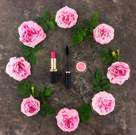 Decorative flat lay composition with cosmetics and flowers. Make up time concept. Top view on dark background Stok Fotoğraf