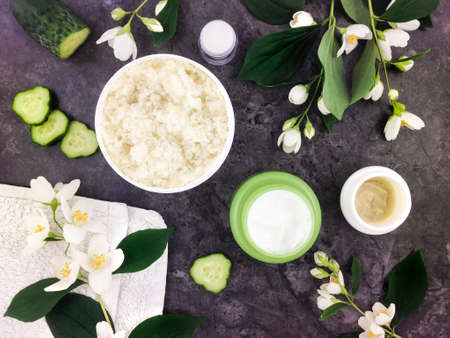 ingredient: Set of spa treatment products and jasmine flowers on stone background. Flat lay