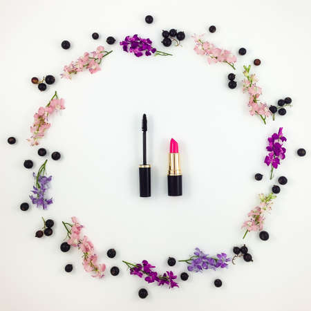 Decorative colorful flat lay composition with cosmetics, bright flowers and berries. Top view on white background Stock Photo