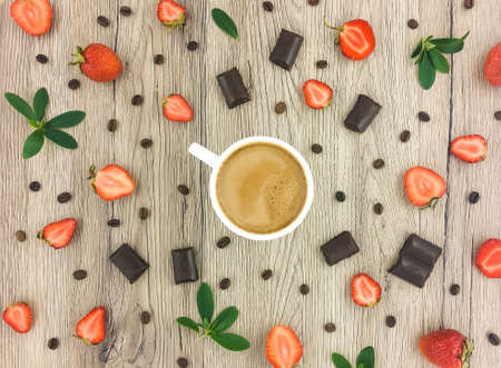 strawberry chocolate: Cup of coffee with milk, chocolate, strawberries and coffee beans on wooden background. Flat lay, top view