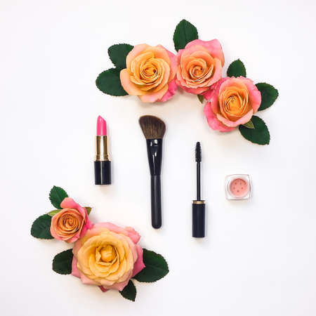 Decorative flat lay composition with woman cosmetics and rose flowers. Flat lay, top view on white background, make up concept Stock Photo