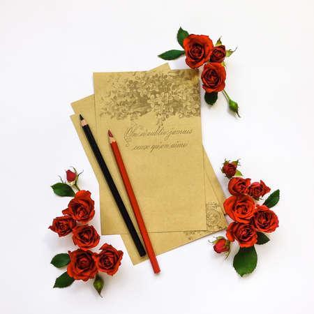 rosas rojas: Composición decorativa de hojas de papel vacíos con lápices y rosas rojas sobre fondo blanco. aplanada, vista desde arriba, la escritura o el concepto de la pintura Foto de archivo
