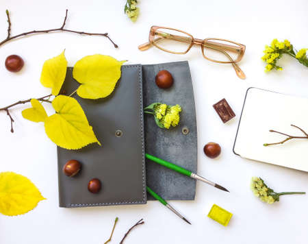 flat brush: Closeup of leather pen case, and art accessories and glasses on white background. Decorated with autumn yellow leaves, flowers and branches. Top view, flat lay