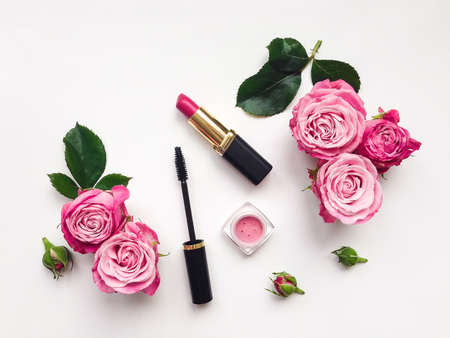 Decorative flat lay composition with mascara, lipstick and blush, decorated with flowers. Top view on white background, view from above