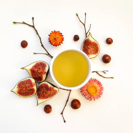 coffee harvest: Bright morning cup of tea with fig fruits. Autumn decoration: yellow dry flowers, chestnuts and tree branches. Flat lay, top view, view from above