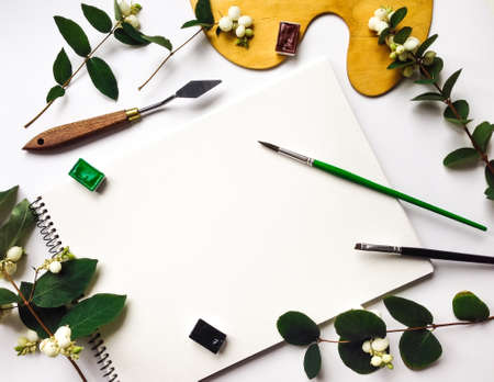 flat brushes: Autumn composition with album, watercolors and brushes on white background, decorated with green snowberry branches and berries. Flat lay, top view, view from above