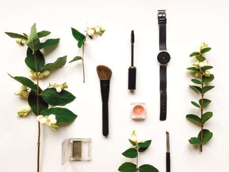 flat brush: Colorful composition with woman watch, make up tools and accessories, decorated with green snowberry branches and berries. Flat lay on white table, top view, view from above Stock Photo