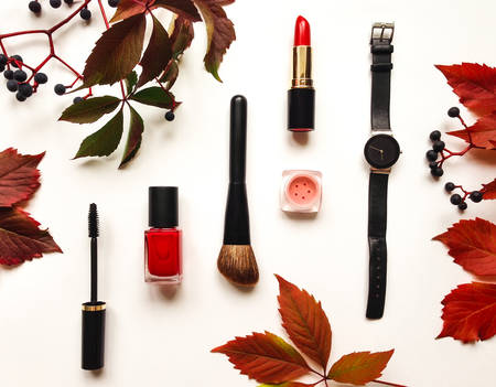lip stick: Decorative flat lay composition with cosmetics, woman accessories, decorated with autumn leaves and berries. Flat lay, top view on white background, fashion still-life