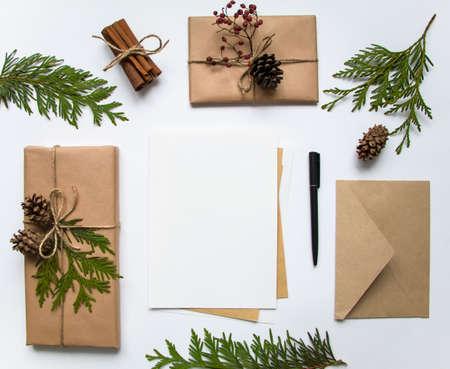papier a lettre: Boîtes à cadeaux vintage en papier artisanal et une lettre sur fond blanc. Présents décorés avec des pièces naturelles. Noël ou autre concept de vacances, vue de dessus, plat Banque d'images