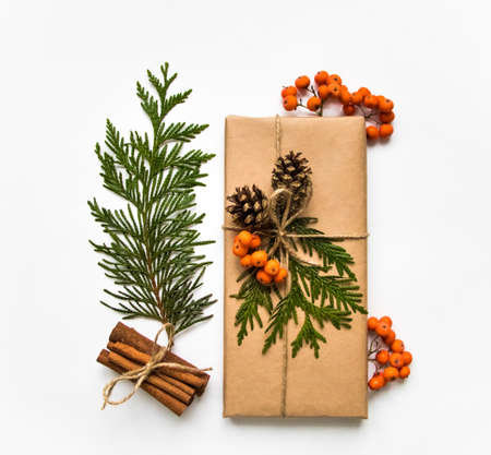 christmas present box: Vintage gift box in craft paper on white background. Present decorated with thuja branches, cones and rowanberries. Christmas or other holiday concept, top view, flat lay